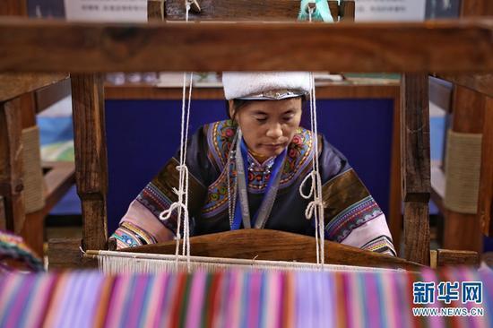 云南展区,一位工作人员现场展示传统纺织工艺。(新华网 张翼鹏 摄)