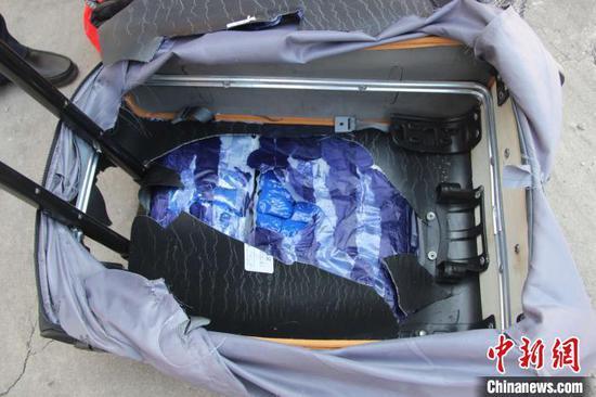图为民警从乘客携带的行李箱夹层中查获冰毒。 韦立鹏 摄