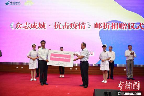 图为中国邮政集团有限公司云南省分公司向云南省卫健委捐赠《众志成城·抗击疫情》邮折。 刘冉阳 摄