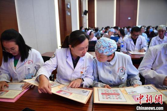 图为云南援助湖北医疗队代表翻阅《众志成城·抗击疫情》邮折。 刘冉阳 摄