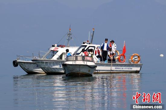 工作人员乘船打捞湖中的水下地笼、虾笼。