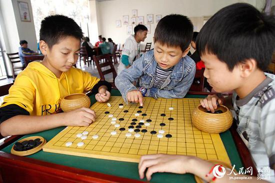 孩子们在卯家湾安置区党群服务中心下棋。