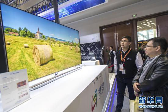 """在武汉东湖新技术开发区举办的第十五届""""中国光谷""""国际光电子博览会上,观众在华星光电展区参观""""8K""""显示屏(2018年11月14日摄)。 新华社记者 熊琦 摄"""