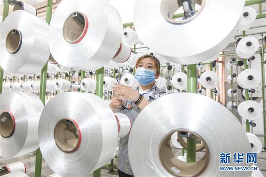 在江苏南通海安经济技术开发区,一家纺织公司的工人在生产线上忙碌(5月15日摄)。 新华社发(向中林 摄)