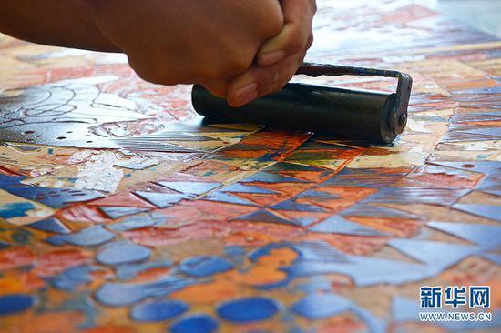 在普洱学院版画工作室内,版画专业的学生李军明使用滚筒涂抹油墨(10月13日摄)。新华网 徐华陵 摄
