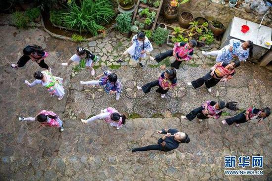 11月21日,在那夺村彩云计划公益志愿服务中心,身穿民族服装的孩子们在张萍(下)带领下练习舞蹈。新华社发(陈欣波摄)