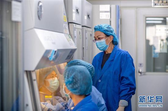 11月25日,云南省艾滋病专家咨询委员会副主任委员贾曼红(右)在指导工作人员进行实验。 新华社记者 胡超 摄
