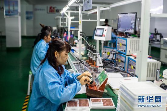 9月29日,搬迁群众在会泽县钟屏街道一家电子扶贫工厂工作。新华社记者 胡超 摄