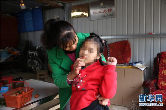 张贵相喂女儿吃自家草莓(2020年12月15日摄)。新华网 彭雪薇 摄