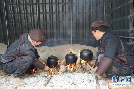 汪程辉(左)和朋友正在往火塘里添柴火(2020年12月30日摄)。新华网发(李丹 摄)