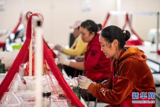 在云南省怒江傈僳族自治州福贡县匹河乡托坪村搬迁安置点,搬迁群众在扶贫车间缝制棒球(2020年11月2日摄)。新华社记者 胡超 摄