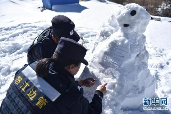 """巡逻途中休息,大家堆起了雪人,边玲玲在雪人上写上了""""信念""""二字。"""