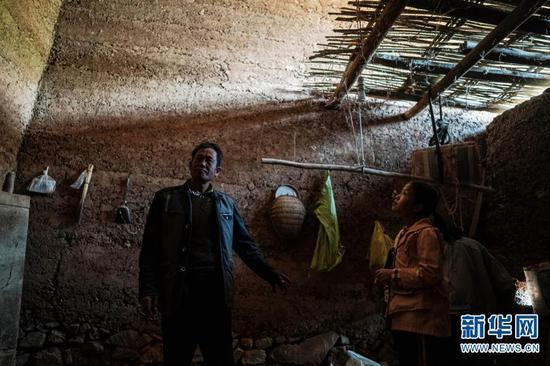 石元顺(左)带着孩子在村里查看旧居(3月15日摄)。