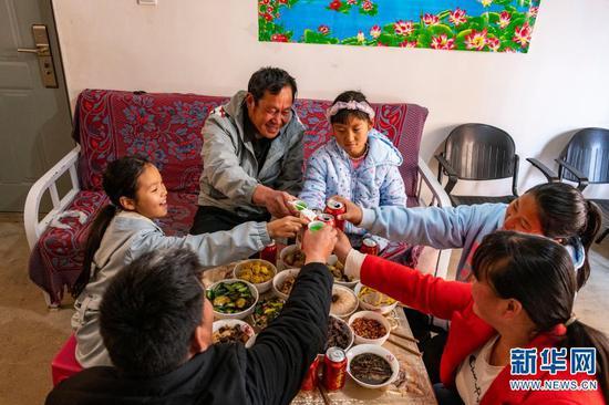 石元顺一家和亲戚们一起吃团圆饭(2月11日摄)。