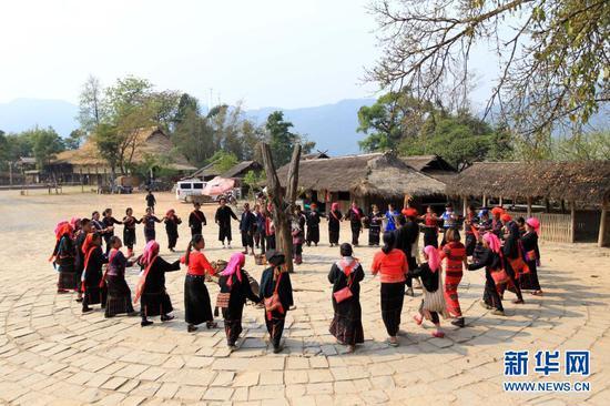 游客与翁丁村佤族村民一起跳圆圈舞(2018年3月22日摄)。新华社记者 井辉辉 摄