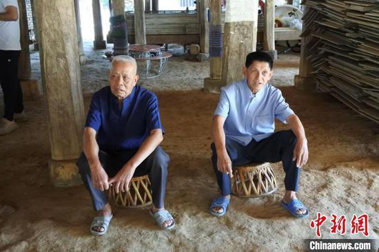 图为83岁曼团村村民波涛岩(左)在曼团联席会议遗址。 中新社记者 罗婕 摄