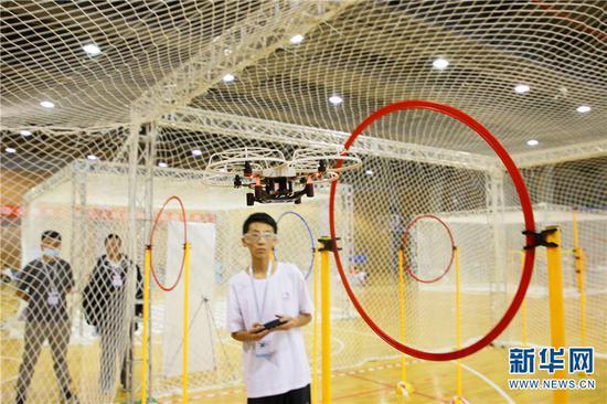 2021年5月29日,参加第35届云南省青少年科技创新大赛的小选手操作无人机穿越障碍。