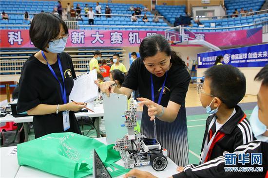 2021年5月29日,第35届云南省青少年科技创新大赛,裁判检查参赛小选手组装好的机器人。