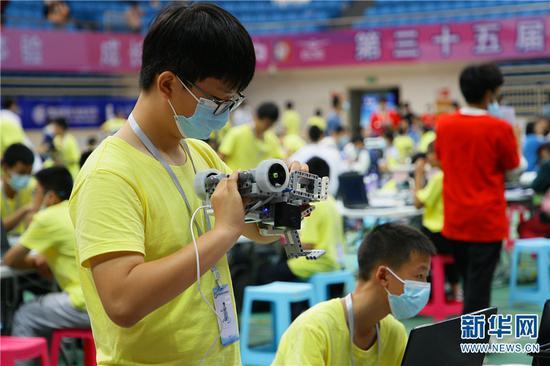 2021年5月29日,参加第35届云南省青少年科技创新大赛的小选手正在调试机器人。