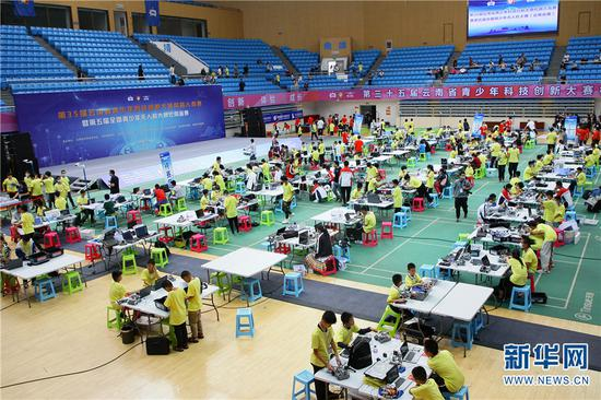 2021年5月29日,参加第35届云南省青少年科技创新大赛的小选手在待赛区调试机器人。