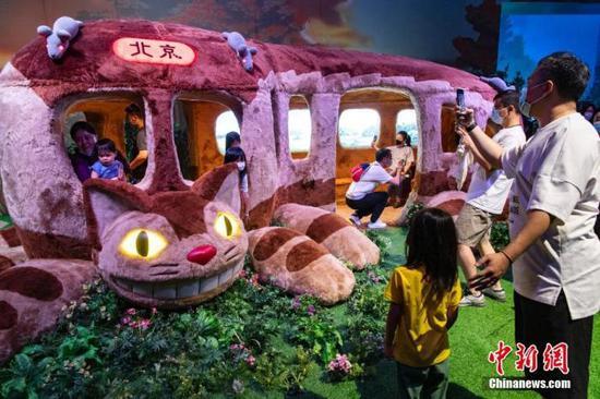"""6月12日,""""宫崎骏与吉卜力的世界""""动画艺术展在北京今日美术馆开展,民众前往观展。图为观众走进""""龙猫巴士""""拍照留念。 中新社记者 侯宇 摄"""