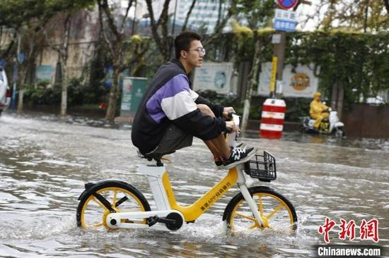 图为8月9日,昆明市民经过淹积水路段。 李嘉娴 摄