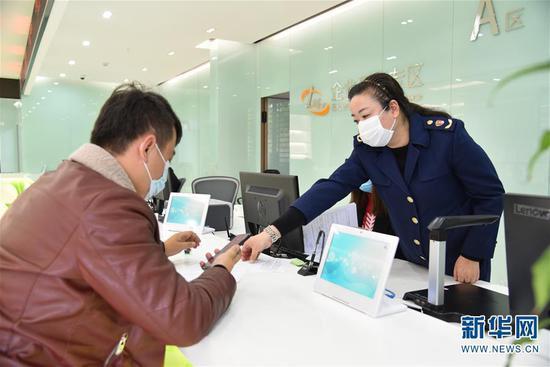 11月3日,企业工作人员(左)在昆明滇池国家旅游度假区政务服务中心办理业务。新华社记者 林碧锋 摄