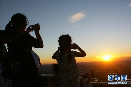 游客在云南曲靖朗目山上看美景。