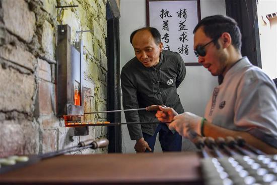 李国伟在云南保山市永子棋厂指导弟子(5月12日摄)。