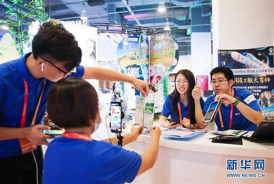 在服贸会旅游服务专题展区,中国旅游集团展位的工作人员通过直播向线上观众介绍旅游服务产品(9月5日摄)。 新华社记者 潘思危 摄