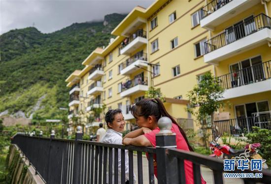 搬迁至怒江傈僳族自治州泸水市大龙塘安置点的居民在家门前聊天(9月15日摄)。新华社记者 江文耀 摄