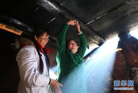 在云南怒江贡山县丙中洛镇,管延萍(左)指导一名村民进行康复训练(1月13日摄)。