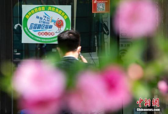 4月6日,北京市西城區金融街的一處商鋪入口處張貼有新冠疫苗接種綠色標識。中新社記者 侯宇 攝