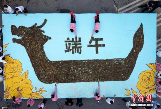 6月13日,中国传统节日端午节前夕,河南洛阳老君山,民众用3000枚槲棕和小米拼成《牡丹龙舟棕》过端午佳节。图片来源:ICphoto