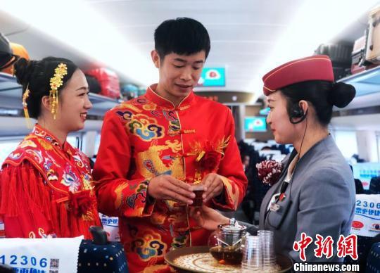 图为动车乘务员为新郎新娘送上祝福的茶水。胡芃 摄
