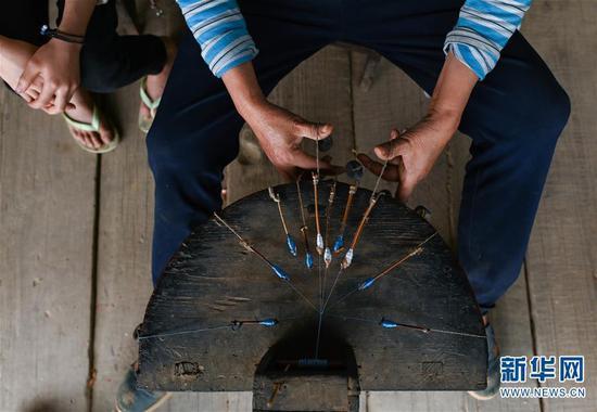 4月6日,板江村村民李中利用传统工艺编服饰的花边。 新华社记者 江宏景摄