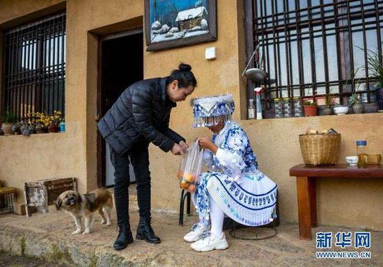 11月21日,在那夺村彩云计划公益志愿服务中心,张萍(左)在舞蹈练习结束后给一名孩子送水果。新华社发(陈欣波 摄)