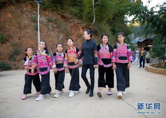 11月21日,张萍(右三)带领孩子们走在那夺村里。新华社发(陈欣波 摄)