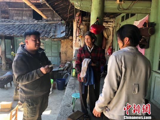 图为拍摄小组成员了解村民家庭情况 杨志禧 摄