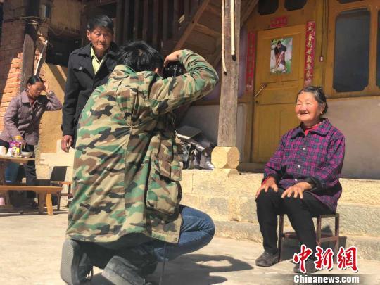 图为杨董清向村民展示拍摄的照片 杨钏杰 摄