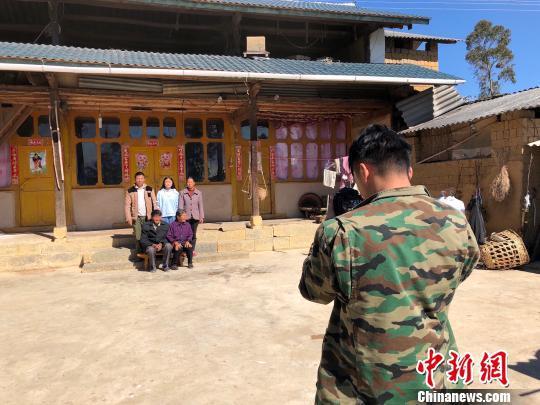 图为杨董清正在为村民拍摄全家福 杨志禧 摄