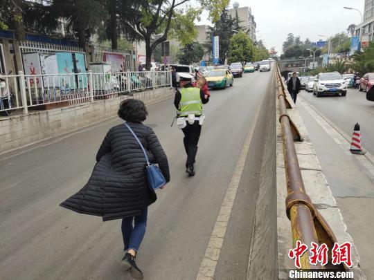 图为交警接过孩子奔向医院。曲靖交警提供