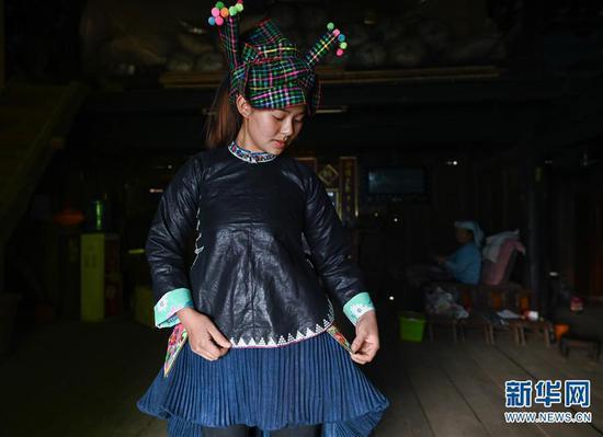 4月6日,板江村村民李广利展示传统的壮族妇女服饰。 新华社记者 江宏景摄