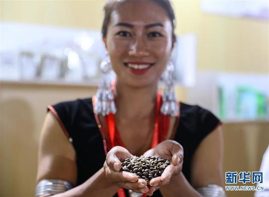 在第二届普洱国际精品咖啡博览会上,云南省普洱市孟连傣族拉祜族佤族自治县的佤族姑娘赵梅展示自家种植、加工的精品咖啡豆(3月15日摄)。新华社记者 何春好 摄