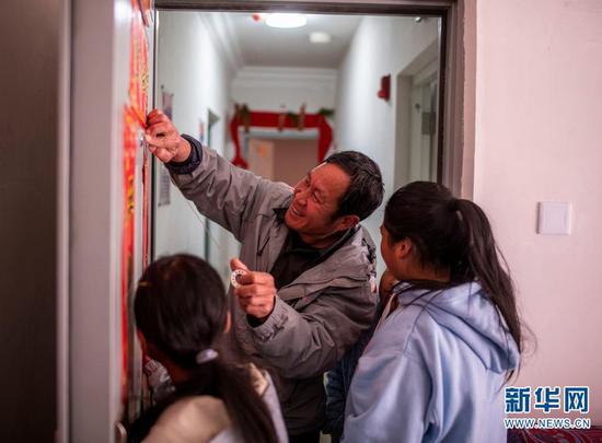 石元顺带着孩子们在新家门口贴春联(2月11日摄)。