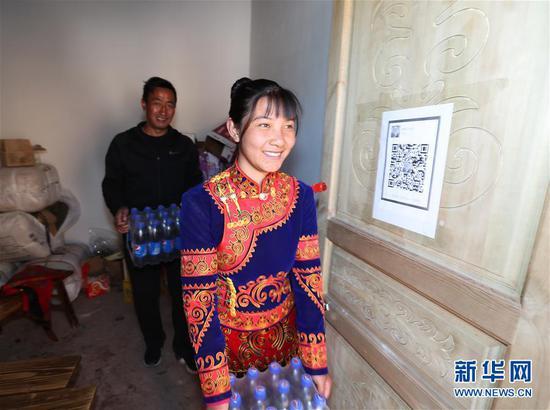 吉好也求的大女儿吉好有作在四川昭觉县三岔河乡三河村新居小卖部里搬饮料(2019年2月11日摄)。新华社记者 江宏景 摄