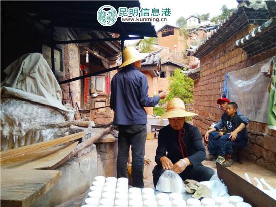 杨斌全(戴草帽站立者)与老伴正在制作诺邓井盐。记者江枫/摄