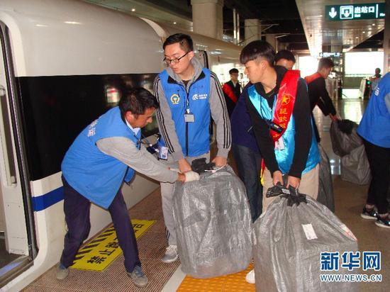 青年志愿者和搬运人员正将包裹搬运到动车内。(供图)
