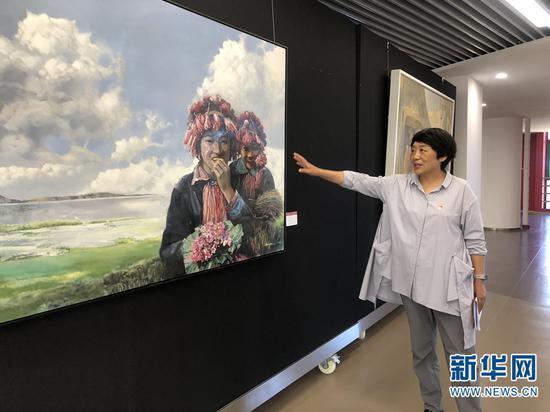 黄雁玲介绍展出的优秀作品。新华网 柴静 摄