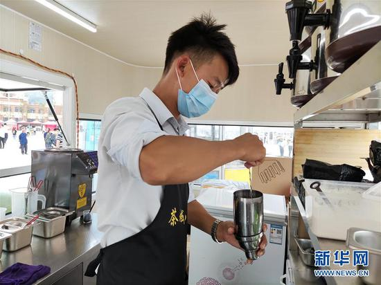 云南昭通靖安新区的搬迁农民王仕坤在制作奶茶(8月8日摄)。 新华社记者 林碧锋 摄